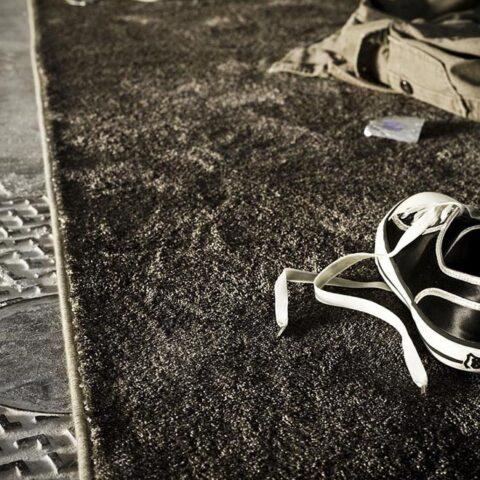 ropa y zapatillas tiradas sobre alfombra moderna efekto seda kp alfombras a medida