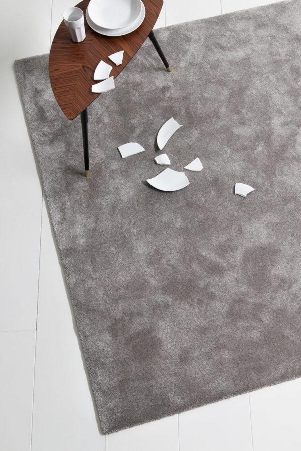mesa y plato roto sobre alfombra a medida queen de kp
