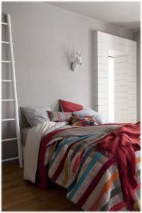 Composición de cojin akito vivaraise sobre una cama