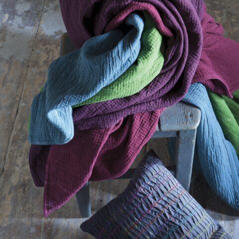 Plaids vivaraise sobre una silla vintage y cojin romane vivaraise apoyado sobre el suelo contra la silla.