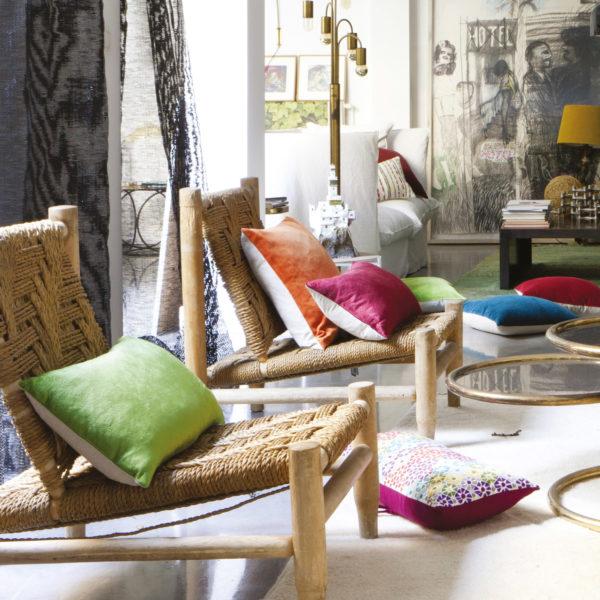 Fotografía de cojines vivaraise dispersos entre el suelo y tumbonas de mimbre en una habitación con cortinas, alfombras y un cuadro al fondo.