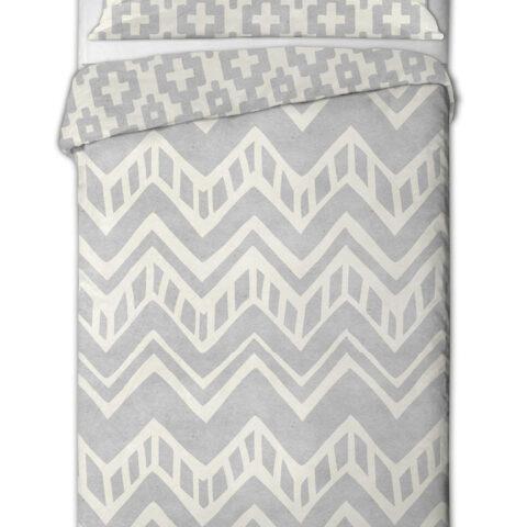 Cama vestida sobre fondo blanco con funda nórdica azteca en tonos grises. Funda nórdica de tela de camiseta.