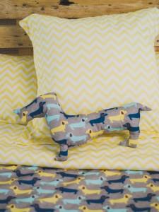 Cojin perro sobre cama vestida con funda nórdica dogs kids.