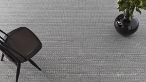 Silla negra y jarrón con flores sobre alfombra de vinilo keplan zeta zeta de kp alfombras a medida