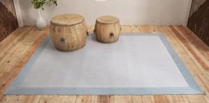 habitación con el suelo de madera con alfombra de vinilo keplan zeta zeta en color azul de kp alfombras a medida