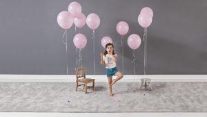 Niña pequeña con globos rosas sobre alfombra takto coor gris de kp alfombras a medida