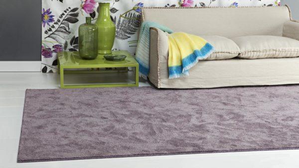 Salón con sofa beige y mesa verde al lado de una alfombra ecológica organik morada de kp alfombras a medida