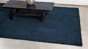 detalle amplaido de mesa de madera antigua sobre alfombra de pelo largo happy luxe kp alfombras a medida