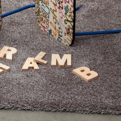 letras y silla tiradas sobre alfombra de pelo largo happy luxe de kp alfombras a medida