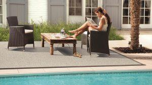 mujer sentada leyendo al borde de la piscina sobre alfombra de exterior alfresko kp alfombras a medida