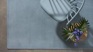 silla azul y maceta sobre alfombra moderna ikon kp alfombras a medida