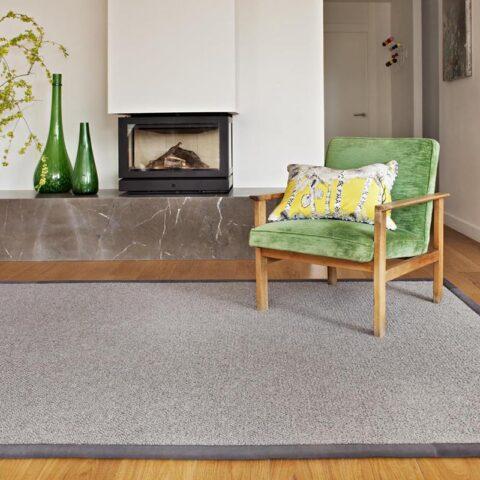 Salón con butaca de terciopelo color verde sobre alfombra de lana kansei kp alfombras a medida en color gris