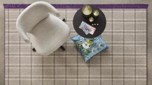 silla, mesa y cojín sobre alfombra de lana cuadros escoceses con remate de flecos morados scoth and walles kp alfombras a medida