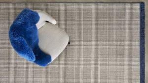 Silla con manta azul sobre alfombra de lana scoth and walles kp alfombras a medida