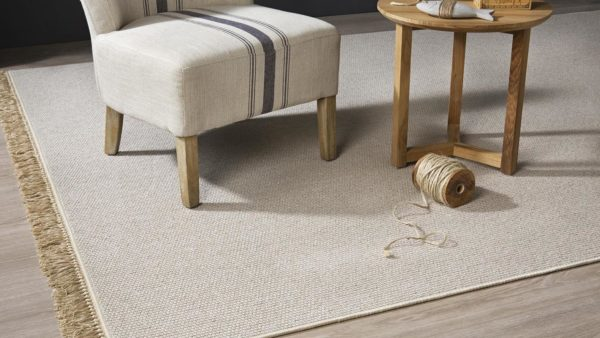 Sillón, mesa, y novillo de lana sobre alfombra de lana muy fina en color natural nakar kp alfombras a medida