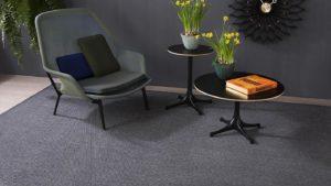 sillón y mesas redondas negras sobre alfombra de lana nakar kp alfombras a medida
