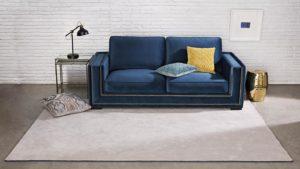 sofá en terciopelo azul sobre alfombra de pelo largo gris i love it kp alfombras a medida
