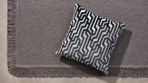 alfombra nórdica kuadro de kp alfombras a medida con flecos y un cojín encima