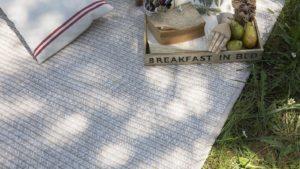 alfombras de exterior spart two kp alfombras a medida en color beige extendida en el cesped para hacer un picnic