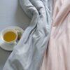 Ropa de cama sisomdos en gris y rosa con taza de te al lado