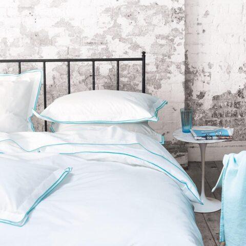 Ambiente con cama vestida con funda nórdica designers guild astor aqua