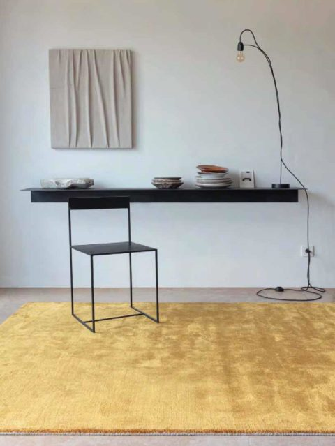 Alfombra ligne pure glow color oro en espacio moderno con una silla sobre ella