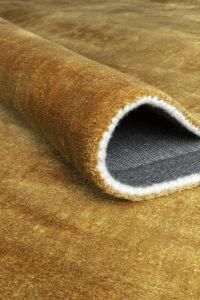 detalle de alfombra doblada ligne pure oro