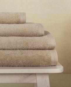 juego de toallas de baño new plus color linen sobre taburete
